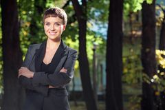Attractive smiling young woman keeping arms crossed at the park. Outdoors portrait of confident attractive caucasian smiling young woman in formal wear keeping Royalty Free Stock Photography