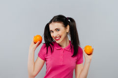Attractive smiling young woman posing with two fresh oranges over gray background. Royalty Free Stock Images