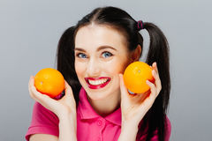 Attractive smiling young woman posing with two fresh oranges over gray background. Stock Photos