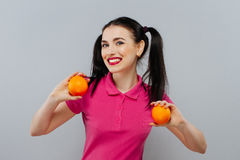 Attractive smiling young woman posing with two fresh oranges over white background Stock Image