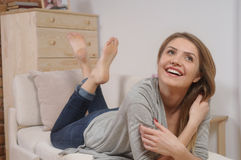 Attractive smiling young woman resting on sofa at home Royalty Free Stock Photo