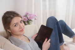 Attractive smiling young woman resting on sofa at home Royalty Free Stock Image