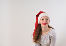 Attractive smiling young woman in santa hat on white background Royalty Free Stock Image