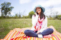 Attractive smiling young woman talking smartphone. Attractive smiling young woman dressed casually talks to the phone sitting on a colourful blanket in the park Stock Photography