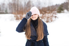 Attractive smiling young woman walking in winter forest in knitt Stock Image