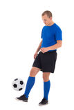 Attractive soccer player in blue uniform playing with ball isola Royalty Free Stock Photography