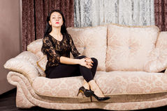 Sophisticated woman posing on a sofa. Attractive sophisticated woman posing elegantly on a sofa in a black evening outfit in a stylish living room Royalty Free Stock Photography