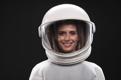 Attractive spacewoman is expressing gladness. Feeling happiness. Portrait of charming delighted female astronaut wearing helmet and protective suit is standing stock photo
