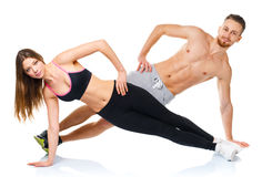 Attractive sport couple - man and woman doing fitness exercises Stock Photos