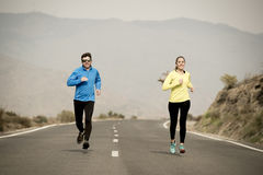 Attractive sport couple man and woman running together on asphalt road mountain landscape Stock Photos