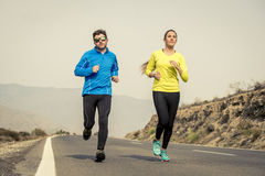 Attractive sport couple man and woman running together on asphalt road mountain landscape Royalty Free Stock Image
