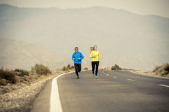 Attractive sport couple man and woman running together on asphalt road mountain landscape Stock Images