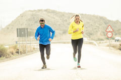 Attractive sport couple man and woman running together on asphalt road mountain landscape Royalty Free Stock Photo