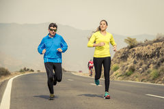 Attractive sport couple man and woman running together on asphalt road mountain landscape Stock Photo