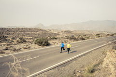 Attractive sport couple man and woman running together on desert asphalt road mountain landscape Royalty Free Stock Photo