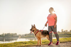 Attractive sport girl  with dog by the river Royalty Free Stock Images