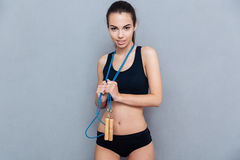 Attractive sport girl holding jumping rope and looking at camera Royalty Free Stock Photos