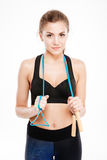 Attractive sport girl holding jumping rope and looking at camera Stock Photos