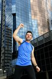 Attractive sport man doing victory and winner sign with his arms after running training in urban business district Royalty Free Stock Images