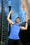 Attractive sport man doing victory and winner sign with his arms after running training in urban business district Royalty Free Stock Image