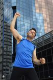 Attractive sport man doing victory and winner sign with his arms after running training in urban business district Royalty Free Stock Photos