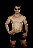Attractive sport man with fit strong bodybuilder body posing cool in corporate gym portrait with sunglasses Royalty Free Stock Images