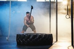 Attractive sport man hitting wheel tire with hammer during training. Attractive sport man with naked torso hitting wheel tire with hammer during training in the royalty free stock images