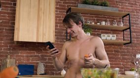 Attractive sport man eating carrot while surfing in internet on smart phone at home. Attractive sport man with naked torso eating carrot and surfing in internet stock video footage