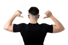 Attractive sport man pointing on his black t-shirt with  copy sp. Advertising corporate back portrait of young attractive sport man with big strong body pointing Stock Images