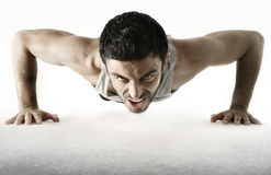 Attractive sport man training push up exercise isolated on white. Attractive young sport man training his body doing push up exercise showing suffering and Royalty Free Stock Images