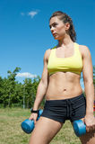 Attractive sport woman with dumbbells on playground Stock Photo