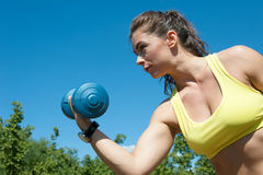 Attractive sport woman with dumbbells on the playground Stock Photography