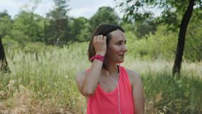 Attractive sportive girl in pink top with headphones listening music on smartphone. Slim brunette girl dancing in park. Young girl. Smiling to camera. Running stock video