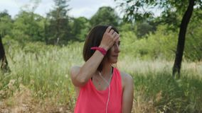 Attractive sportive girl in pink top with headphones listening music on smartphone. Slim brunette girl dancing in park. Young girl. Smiling to camera. Running stock footage