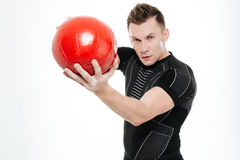 Attractive sportive man doing exercises with heavy fitness ball stock image