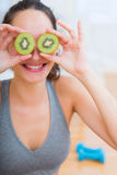 Attractive sportive woman eating kiwi after sport Stock Photography