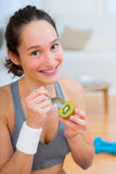 Attractive sportive woman eating kiwi after sport Royalty Free Stock Photography