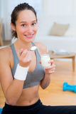 Attractive sportive woman eating yoghurt after sport Stock Images