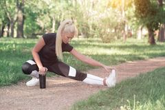 Girl doing stretching exercises. Attractive sportive young girl doing stretching exercises for legs, in the park. Dressed in sportswear Royalty Free Stock Photography