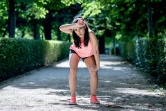 Attractive sports woman runner taking a break feeling tired after running stock images