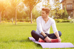 Attractive sportsman doing yoga on grass Royalty Free Stock Photo
