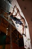 Attractive sportsman putting efforts to boulder artificial climbing wall in bouldering gym indoors. Reaching the top. Attractive sportsman putting efforts to Stock Image