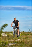 Attractive sportsman riding bike on rocky trail against sky with clouds. Royalty Free Stock Photo