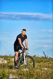 Attractive sportsman riding bike on rocky trail against sky with clouds. Stock Image