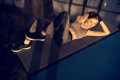 Attractive sportswoman doing abs on mat in sports center royalty free stock photography