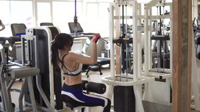 Attractive sportswoman doing an exercise on a training apparatus in the gym. girl doing an exercise on the muscles of. The back stock video