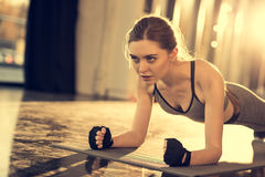 Attractive sportswoman doing plank on mat in sports center royalty free stock photos