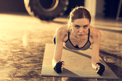 Attractive sportswoman doing plank on mat in sports center royalty free stock image