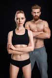 Attractive sportswoman and handsome sportsman posing isolated on black Royalty Free Stock Photos