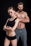 Attractive sportswoman and handsome sportsman posing isolated on black Royalty Free Stock Photography